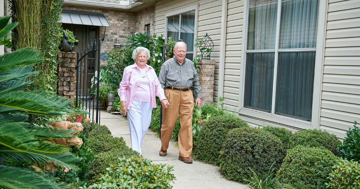 Couple walking in the front of their home.
